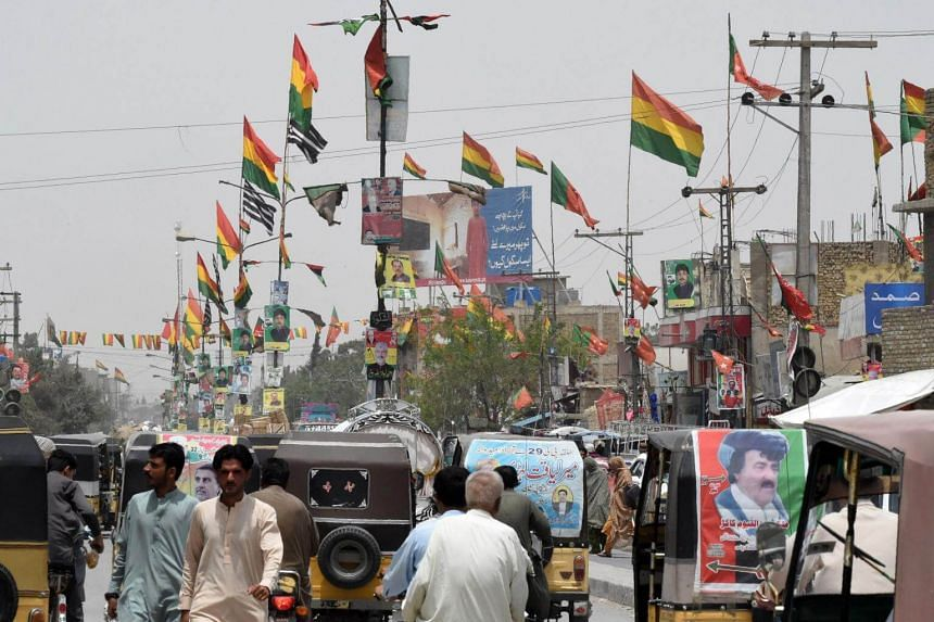 Pakistani commuters drive along a road with posters of candidates taking part in the upcoming general elections, in Quetta, on July 16, 2018.
