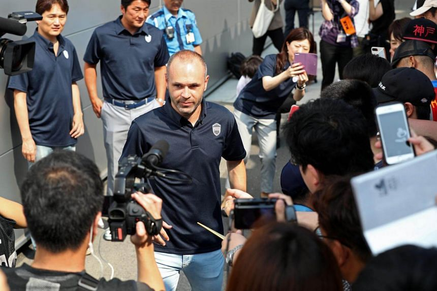 Spanish footballer Andres Iniesta (centre) is surrounded by Japanese fans upon his arrival at Kansai International Airport in Izumisano, Osaka Prefecture, on July 18, 2018.