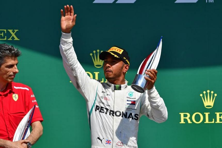 Lewis Hamilton celebrates on the podium after the British Formula One Grand Prix at the Silverstone motor racing circuit in Silverstone, central England, on July 8, 2018.