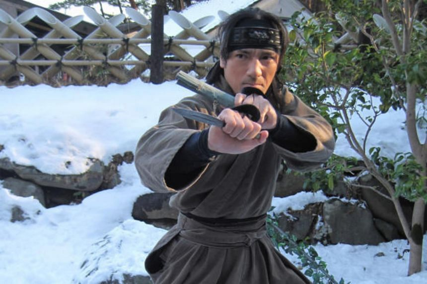 A actor posing as a ninja in a show at the Grand Ninja Theatre at Edo Wonderland, a theme park in Japan.