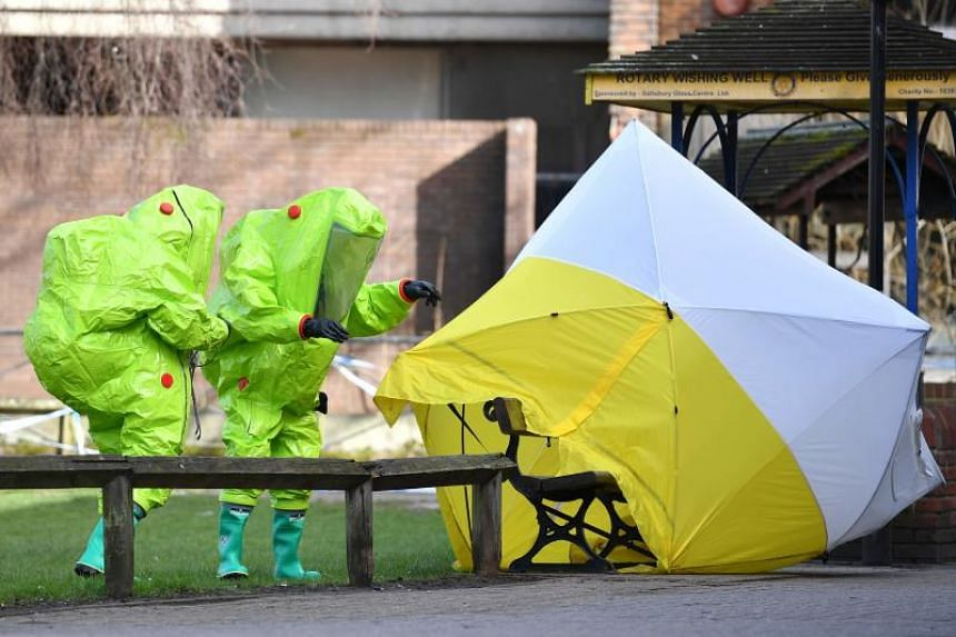 Members of the emergency services fixing a tent over the bench where Sergei Skripal and his daughter Yulia were found, in Salisbury, Southern England, on March 8, 2018.