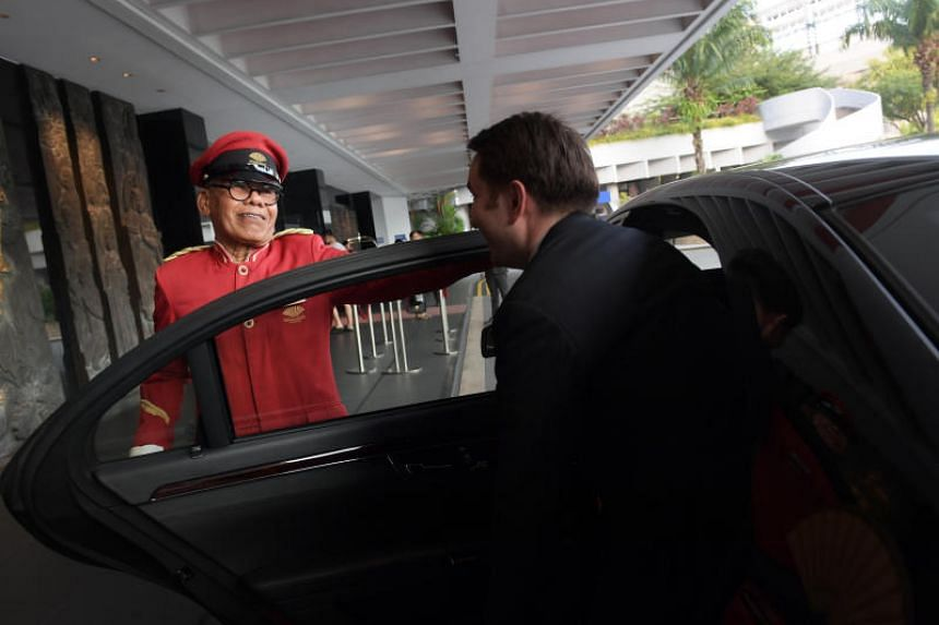 Mr Mohamed Taspir Ahmad, 79, a doorman at the Mandarin Oriental Singapore, opens vehicle doors for guests who arrive at the hotel.