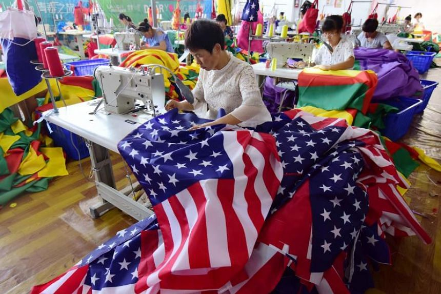 Chinese employees sew US flags at a factory in Fuyang in China's eastern Anhui province on July 13, 2018.