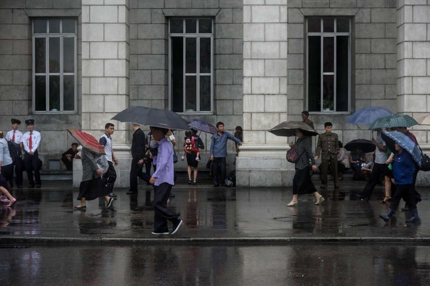 Pedestrians walking past the central railway station in Pyongyang, on June 14, 2018.