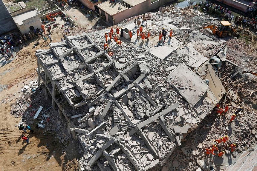 Rescue workers look for survivors amidst the rubble at the site of a collapsed residential building at Shah Beri village in Greater Noida, India on July 18, 2018.
