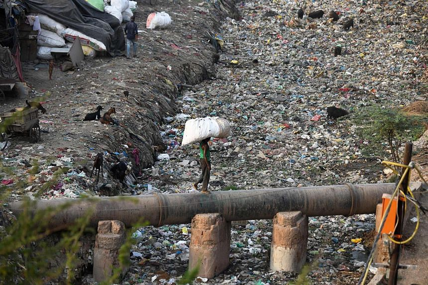 A man carrying a bag containing plastic recyclable items walks on a water pipe next to a sewage drain canal full of garbage in the Taimur Nagar slum area in New Delhi.