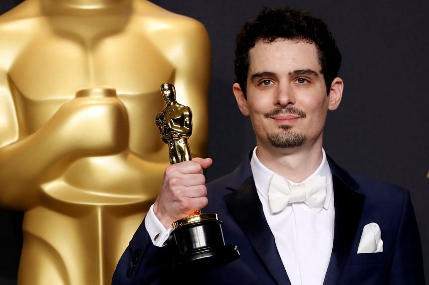 Damien Chazelle poses with his Best Director Oscar for the film La La Land.