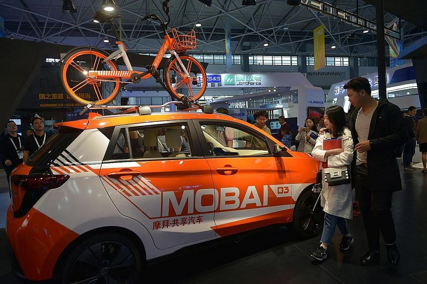 A shared vehicle and a shared bicycle of bike-sharing firm Mobike at the China International Big Data Industry Expo. Firms such as Mobike and ofo have hung on by winning the backing of China's biggest tech giants.