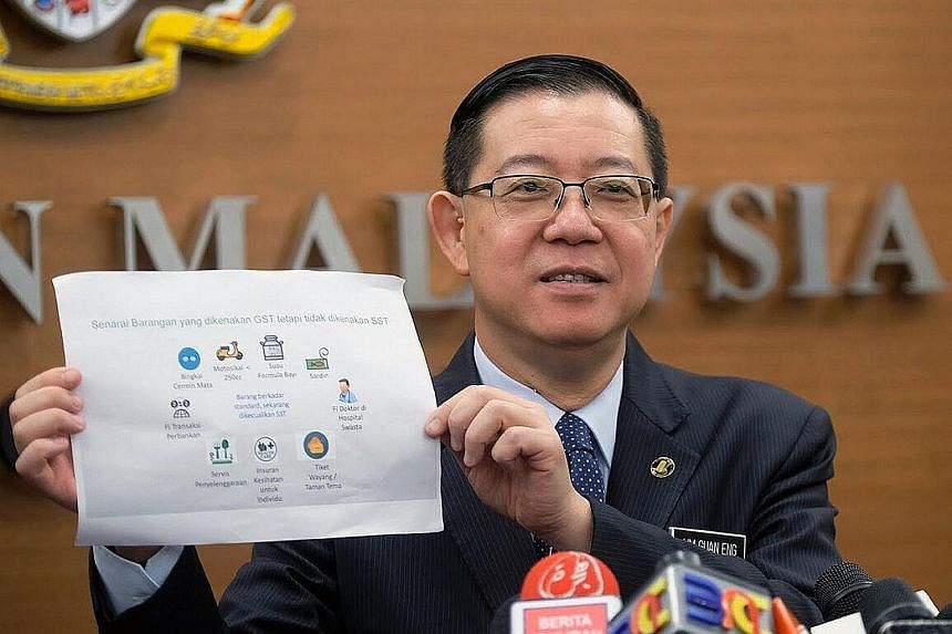 Malaysian Finance Minister Lim Guan Eng with a list of goods which attract GST now but which will not be subject to SST in the future, at a press conference after the Parliament sitting yesterday.