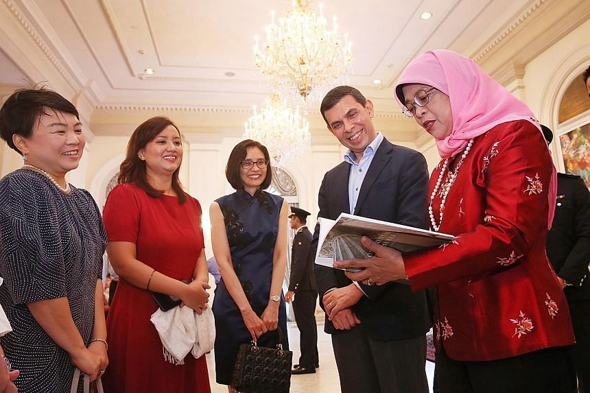 President Halimah Yacob taking a look at Monumental Treasures: Singapore's Heritage Icons with ST editor and ST Press chairman Warren Fernandez. With them are (from left) ST Press general manager Susan Long, book editor Melody Zaccheus and National H