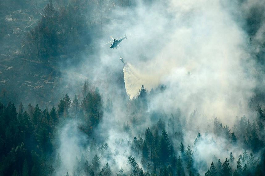 Firefighters using a helicopter to tackle a forest fire burning near Ljusdal, Sweden, on July 18, 2018. The intensity of the fires and extreme weather conditions have prompted Swedes to describe the fires in apocalyptic terms and link them to global