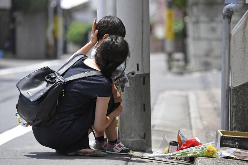 A mother and her child mourn for Yua Funato in front of an apartment where she died in Tokyo, Japan, in this photo taken by Kyodo on June 26, 2018.
