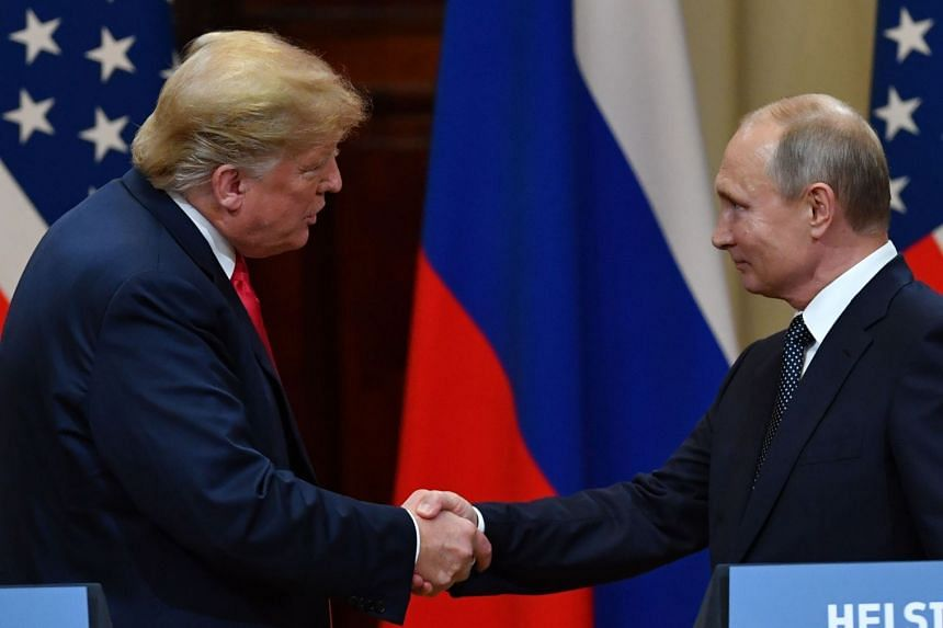 Trump (left) shaking hands with Putin at the end of a joint press conference after their summit.