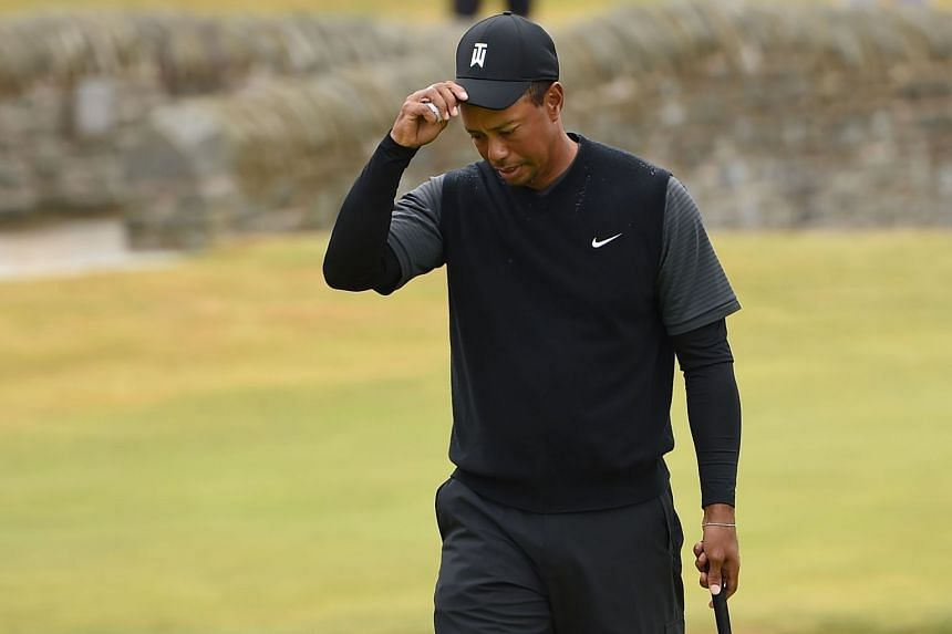 Woods reacts to missing his birdie putt on the 18th green during his second round 71.