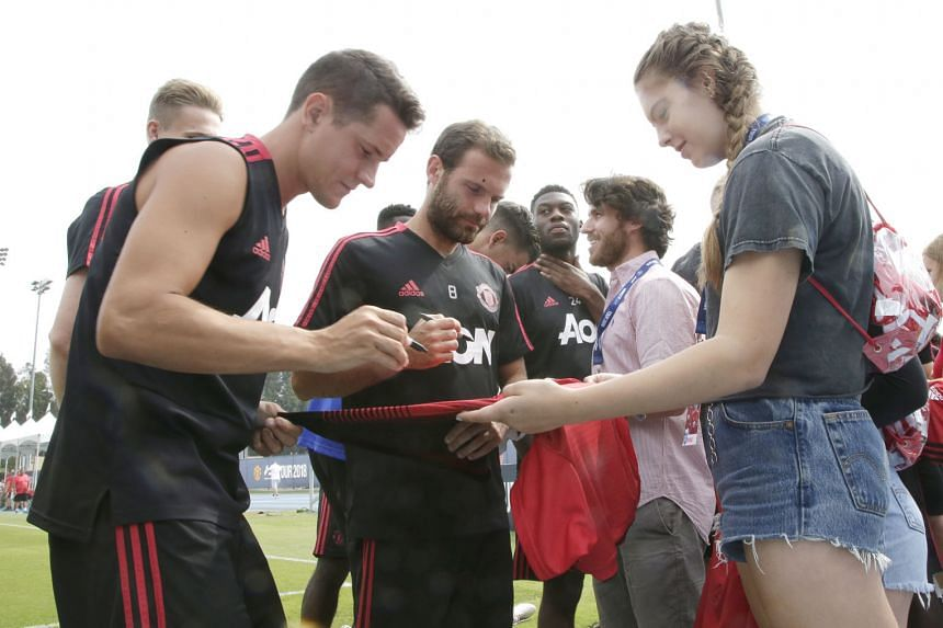 Manchester United players, including Juan Mata (centre), sign autographs for fans before practice at Drake Field at UCLA in Los Angeles. United, depleted by World Cup absentees, face Italian side AC Milan in an International Champions Cup match at th
