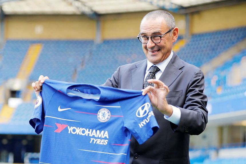 Chelsea's new manager, Maurizio Sarri, holds up a team shirt during his unveiling at Stamford Bridge on Wednesday. Former Chelsea and Italy striker Gianfranco Zola has been appointed his assistant.