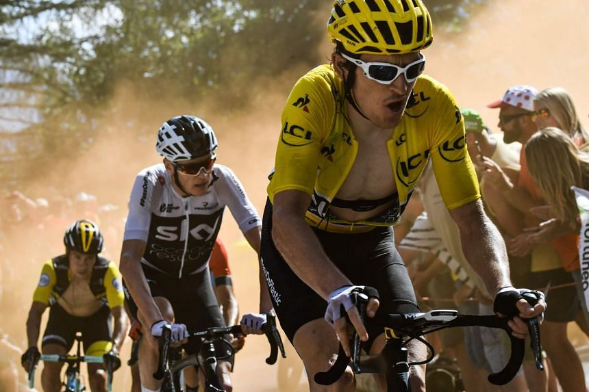 """Thomas, wearing the overall leader's yellow jersey, rides through the so-called """"Dutch Corner"""" in the ascent to l'Alpe d'Huez."""