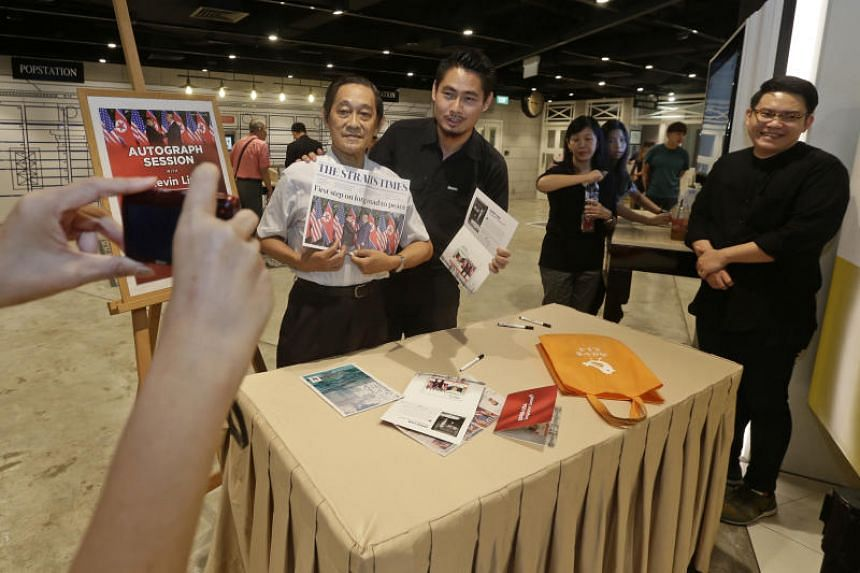 Retired teacher Ng Teng Nam (left), 72, getting a photo taken with Straits Times executive photojournalist Kevin Lim during an autograph session held at the SingPost Centre on July 20, 2018.