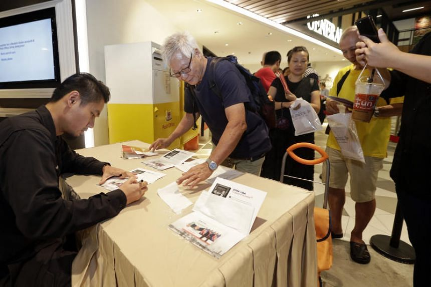 Straits Times executive photojournalist Kevin Lim autographed five sets of commemorative Trump-Kim Summit stamps for Mr Lim Hong (second from left, in black) on July 20, 2018.