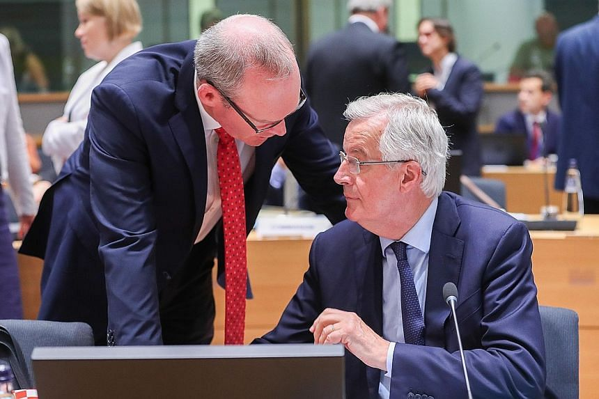 The European Union's chief Brexit negotiator, Mr Michel Barnier (seated), with Irish Minister for Foreign Affairs and Trade Simon Coveney before the General Affairs Council meeting at the European Council in Brussels yesterday.