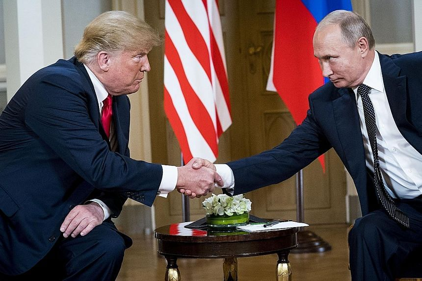 US President Donald Trump meeting President Vladimir Putin of Russia in Helsinki on Monday. The US' top intelligence official is still groping for details of what the two leaders had discussed. Mr Trump speaking to the press during a meeting with mem