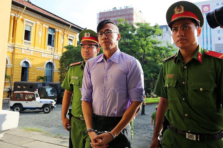 "Mr William Anh Nguyen being escorted by policemen to a courtroom for his trial in Ho Chi Minh City yesterday. The American of Vietnamese descent was accused of ""causing public disorder"" during mass protests last month sparked by concerns over the dev"