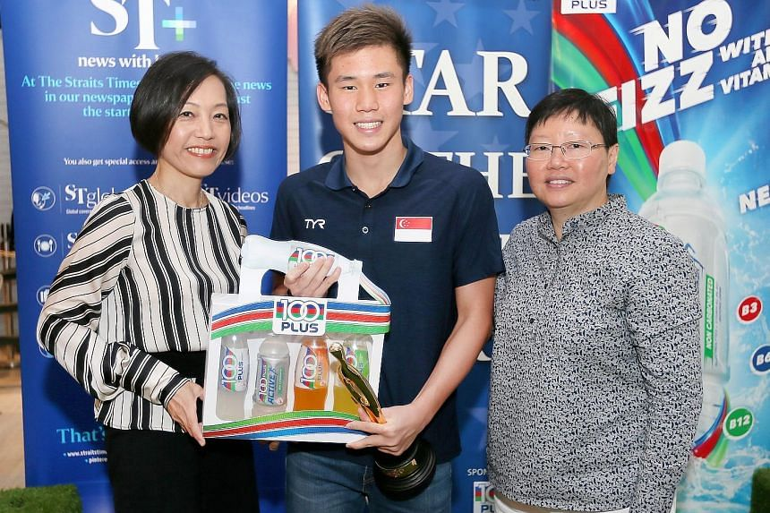 Jennifer See (far left), general manager of F&N Foods, and ST sports editor Lee Yulin, presenting national swimmer Glen Lim with his trophy and hamper.