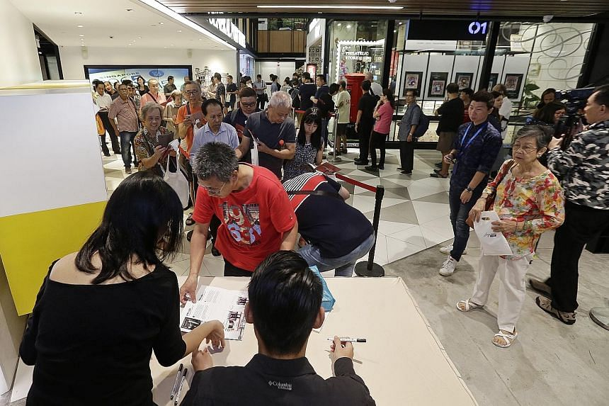 Straits Times photojournalist Kevin Lim signing autographs for those who bought the Trump-Kim summit stamps at the SingPost Centre post office yesterday.