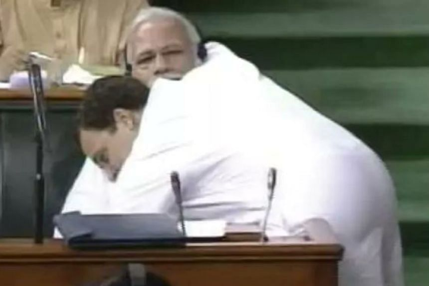 Gandhi interrupted a no-confidence debate by walking across the parliament floor to give his rival a hug.
