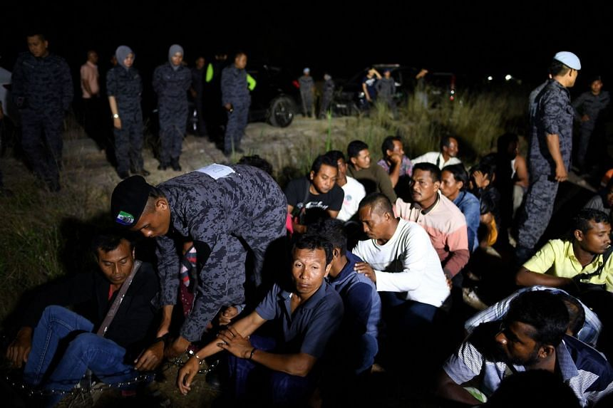 Malaysian immigration officials detaining illegal foreign workers during a raid at a construction site in Port Dickson, on July 11, 2017. The Immigration Department has pledged to ramp up efforts in ridding the country of illegal immigrants.