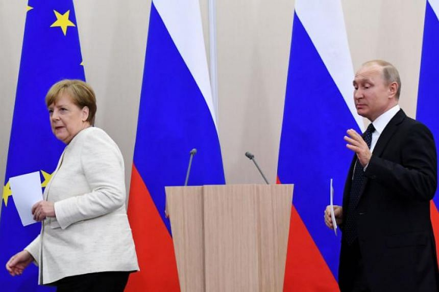 German Chancellor Angela Merkel and Russian President Vladimir Putin seen in a 2018 file photo. He was hours late for a meeting with her in 2014.