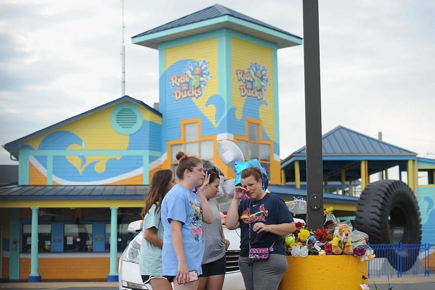 A group of mourners pause for a moment of prayer at Ride The Ducks Tours on July 20, 2018, in Branson, Missouri.