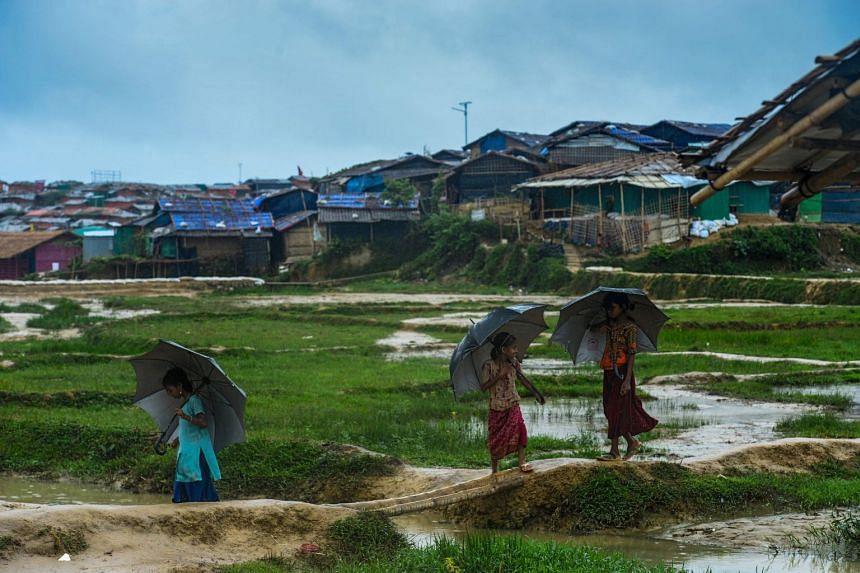 Rohingya refugee children shelter from the rain at Jamtoli refugee camp in Ukhia, Bangladesh, on July 20, 2018