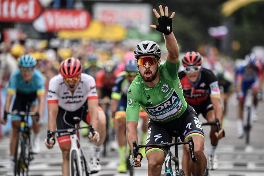Sagan, wearing the best sprinter's green jersey, celebrates as he crosses the finish line to win the 13th stage.