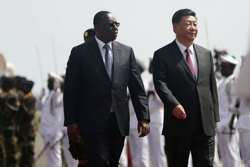 Chinese President Xi Jinping walks with Senegal's President Macky Sall after arriving in Dakar.