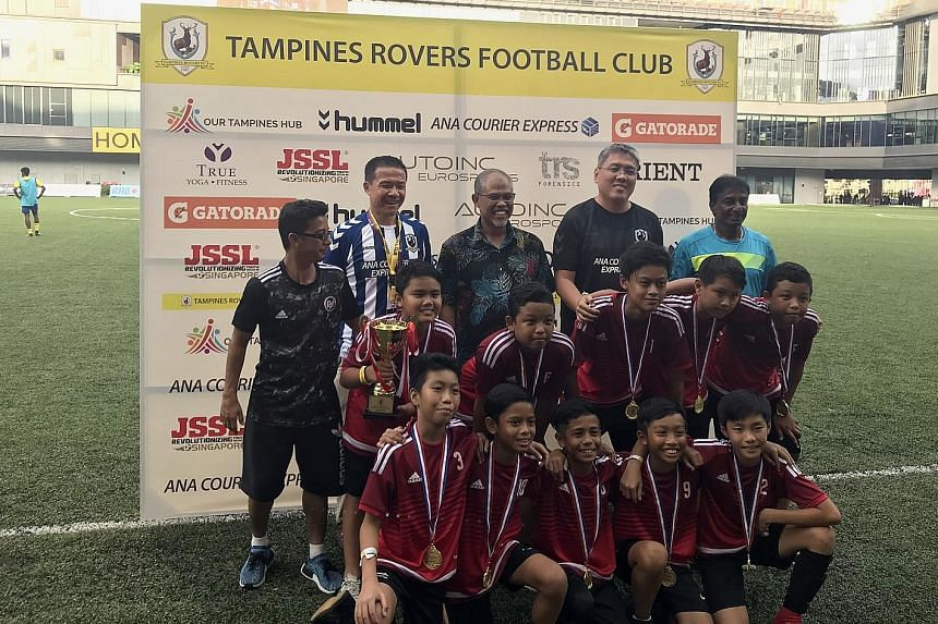 Mr Masagos Zulkifli (centre), Minister for the Environment and Water Resources, after presenting the trophy to players from the Star Soccer Academy who were crowned champions of an Under-12 football festival celebrating Singapore's Racial Harmony Day