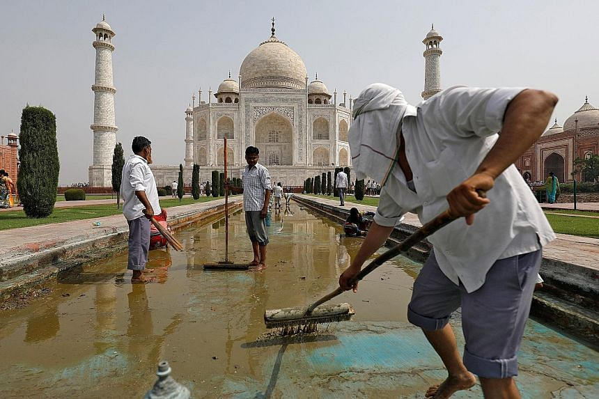 """Workers cleaning the fountain in the historic Taj Mahal complex in Agra, India. Garbage littering the banks of the Yamuna River (below) which flows alongside the Taj Mahal. Experts say it is crucial to restore the river because the """"entire Taj Mahal"""