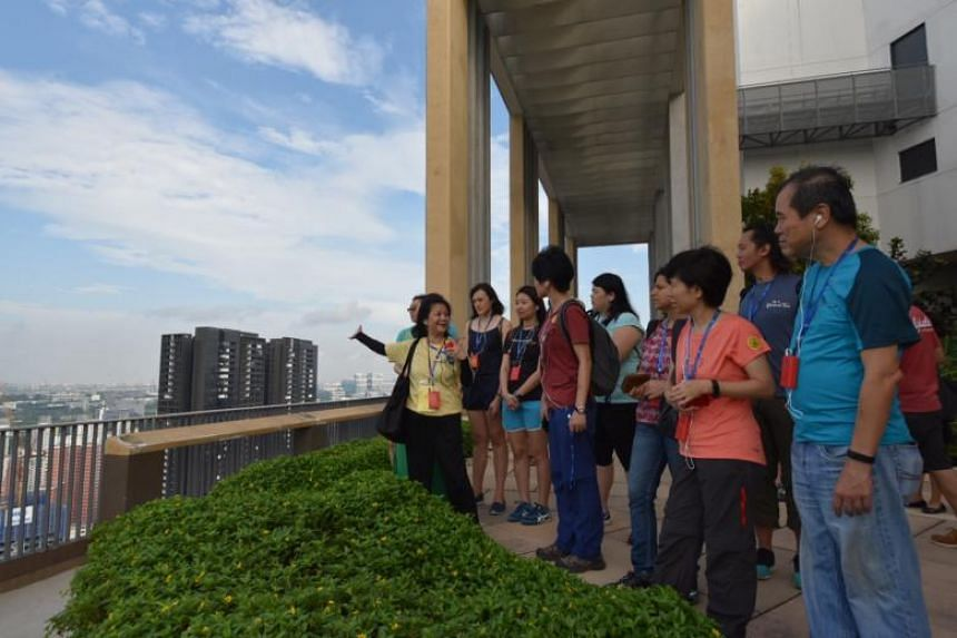 Ms May Hui, 64, a volunteer guide from My Community, leading a group during a heritage trail at the rooftop of Skyville@Dawson, on July 22, 2018.