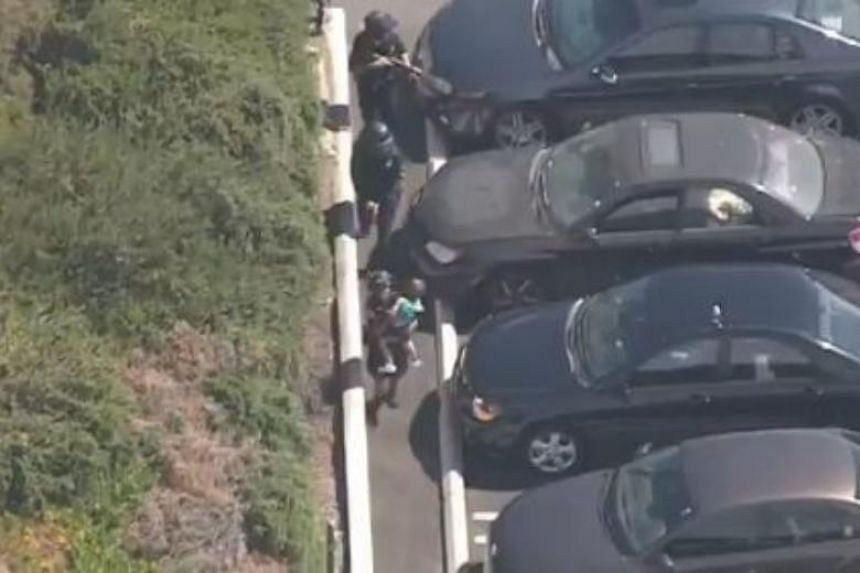 Police officers rescue a group of children after an armed suspect opened fire and barricaded himself inside a Trader Joe's in Silverlake, Los Angeles, on July 21, 2018.