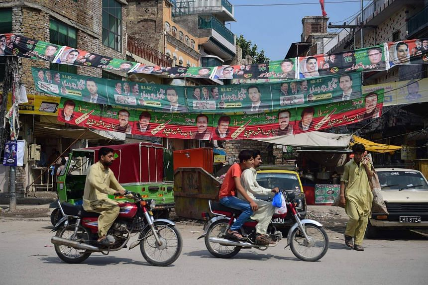 Pakistani youth ride along a road with posters of candidates taking part in upcoming general elections, in Rawalpindi, Pakistan, on July 16, 2018.