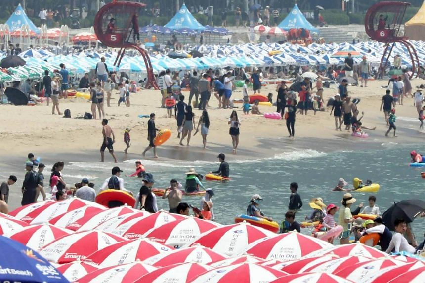 Visitors at Haeundae Beach as a heat wave grips the region, in the southeastern port of Busan, South Korea, on July 15, 2018.