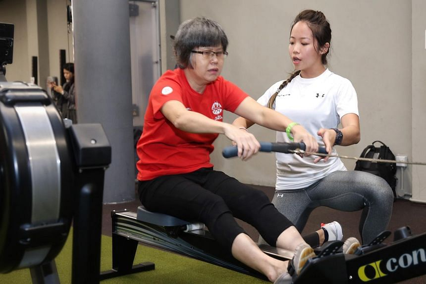 Personal trainer Cheryl Loh advising a participant on the proper use of the equipment at the cardio three-ways programme on July 22, 2018.