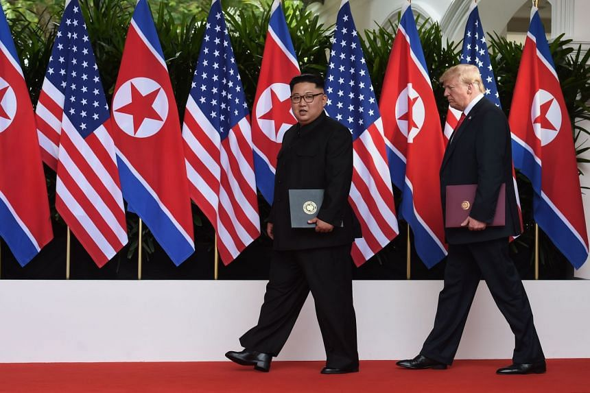 US President Donald Trump (right) walks out with North Korea's leader Kim Jong Un after taking part in a signing ceremony at the end of their historic US-North Korea summit, at the Capella Hotel on Sentosa island in Singapore.