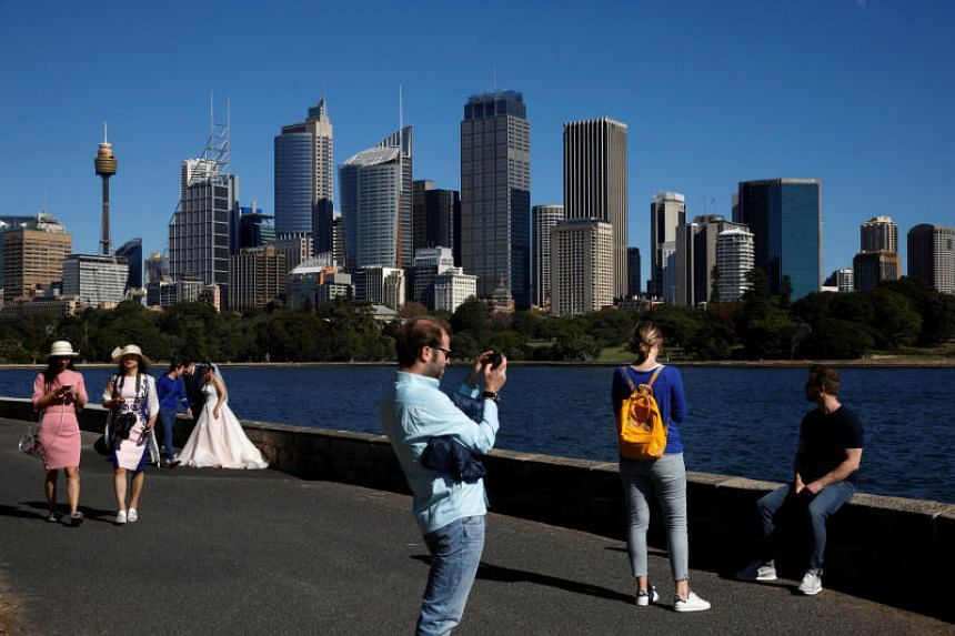 People are seen against the skyline of Sydney in Australia in May 2018.