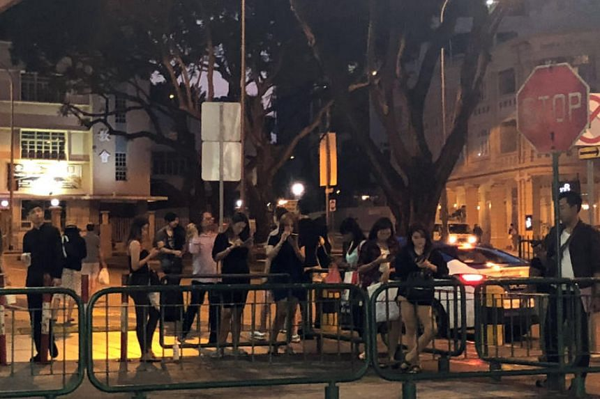 People hanging around near Peace Mansion at night, which is one of reasons why residents of the apartment complex are getting riled up.