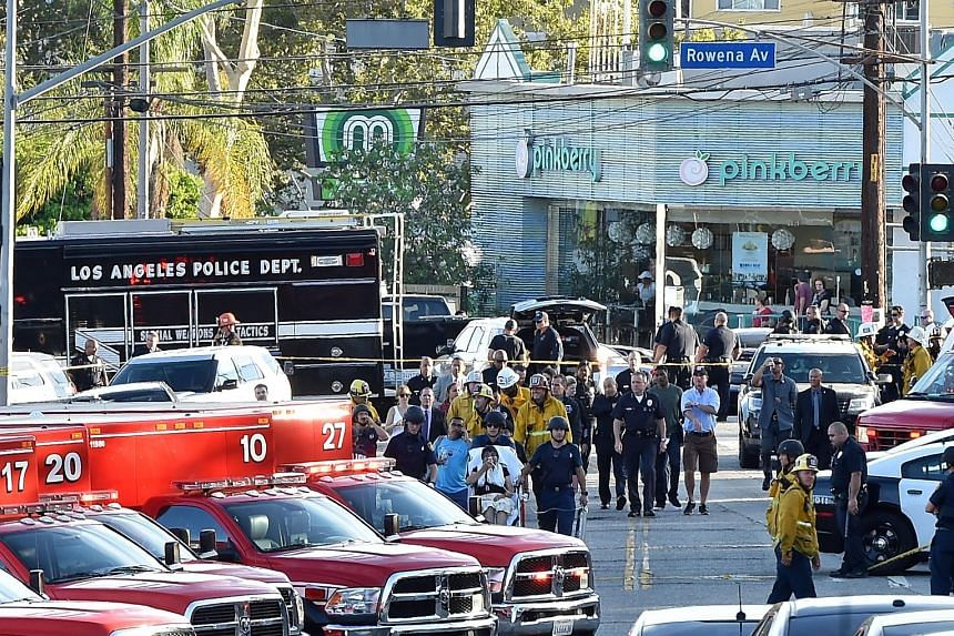 Police and fire department personnel outside a Trader Joe's supermarket (above) in Silverlake, Los Angeles, yesterday, after a man involved in a shooting barricaded himself there and took about 40 people hostage. A Trader Joe's employee (below) being