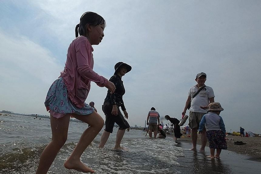 People on the beach of a seaside park in Tokyo yesterday. Japan's severe heatwave has killed at least 15 people and sent more than 12,000 to hospital in the first two weeks of this month.