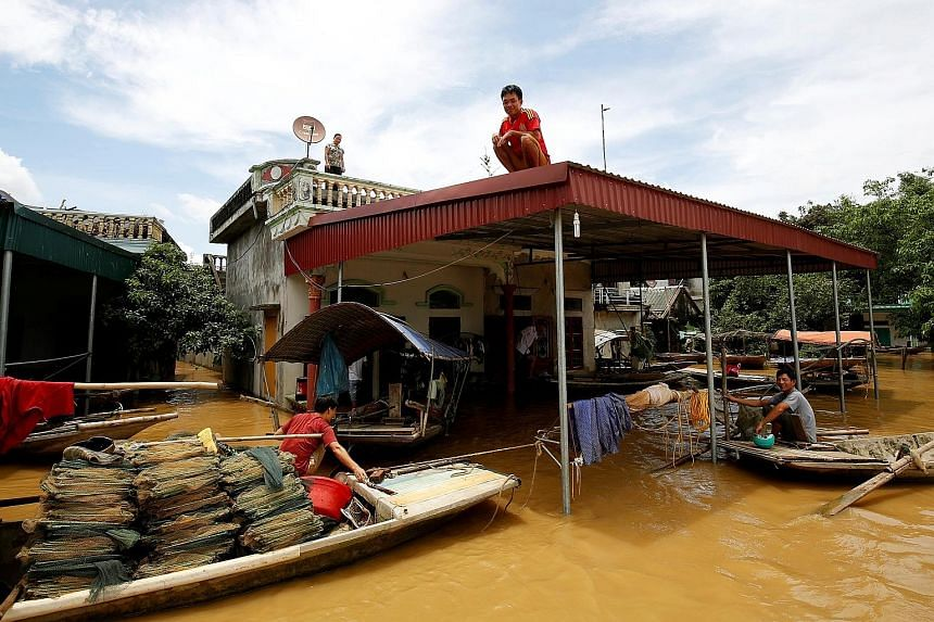 A man on the rooftop of his flooded house after heavy rainfall in Ninh Binh province, Vietnam, yesterday. Flash floods in Vietnam have claimed at least 19 lives, the government said.