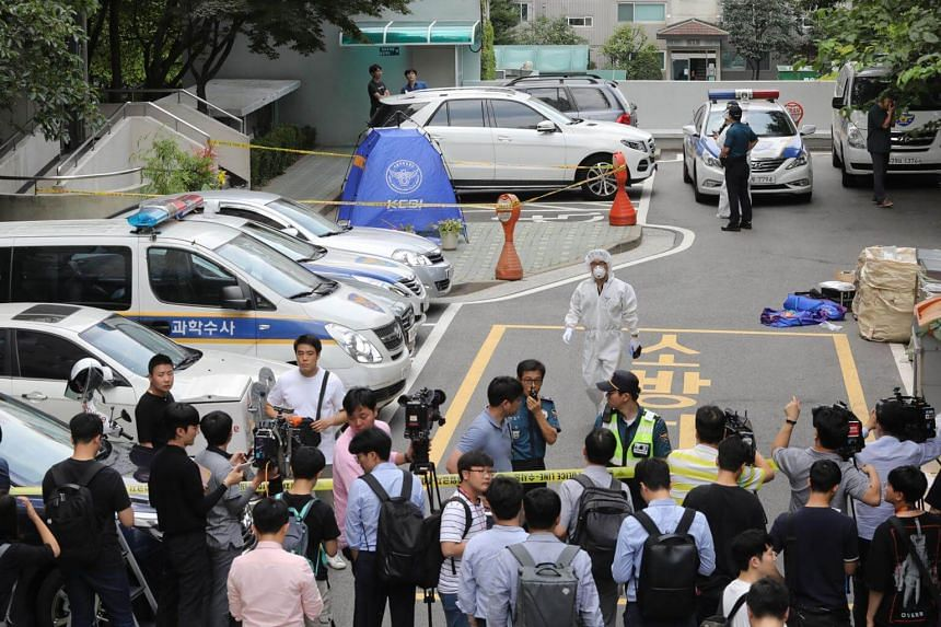 Journalists gather as police inspectors stand next to a tent set up at the spot where Roh Hoe-chan, a three-term lawmaker who was being probed over a bribery scandal, was found dead, on July 23, 2018.