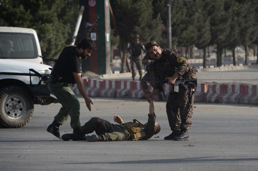 Afghan security forces help an injured colleague after a suicide attack in Kabul on July 22, 2018.